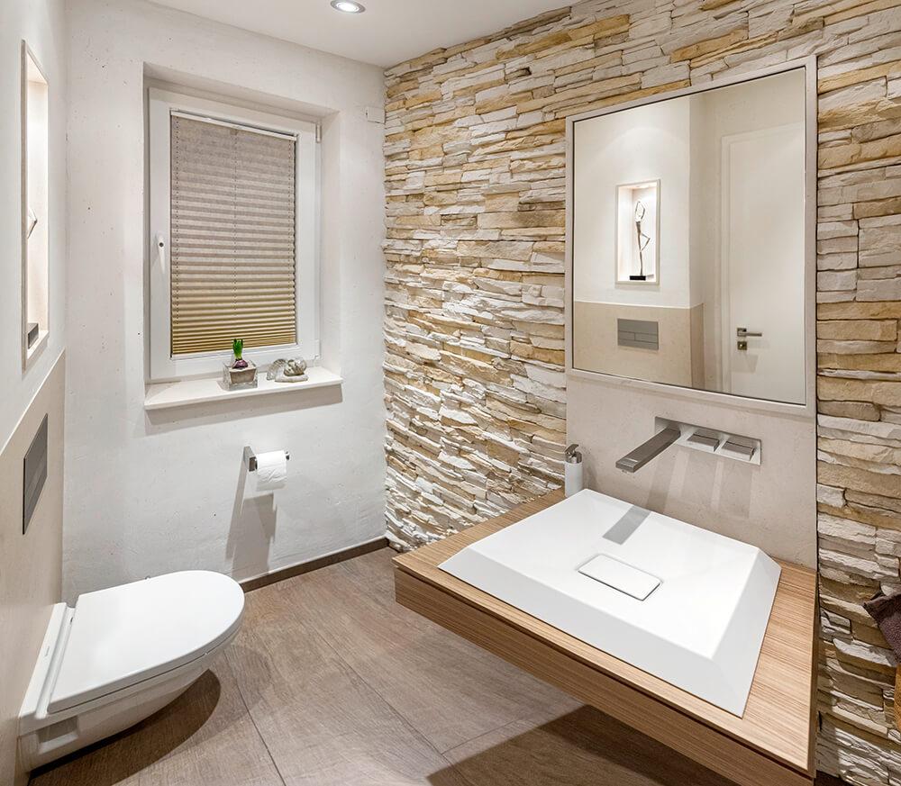 Gäste WC mit Natursteinwand und Design Wandarmatur. Nischenfach mit Beleuchtung als Hingucker in Kamen.